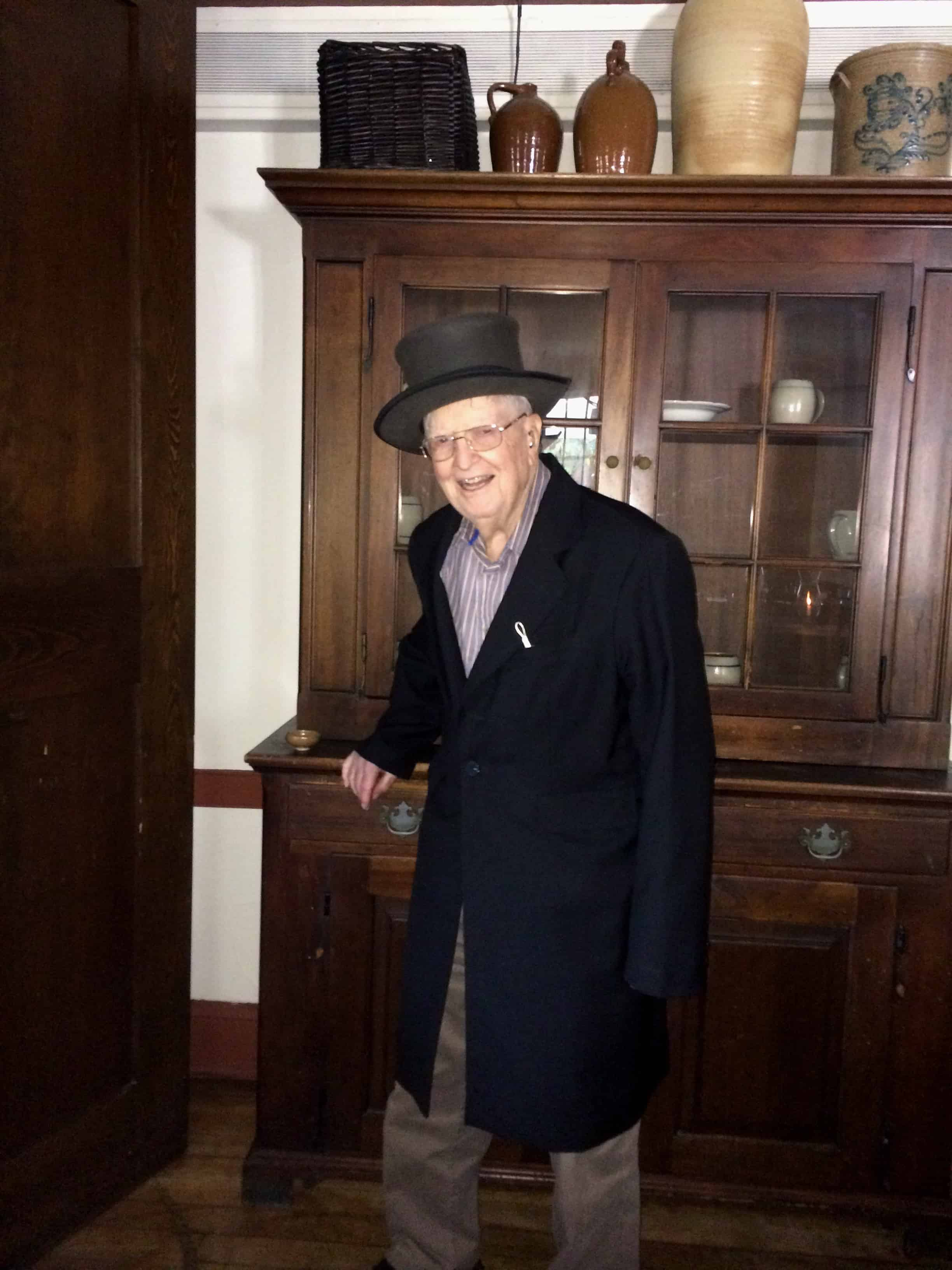 Dad isn't one to sit. He wandered off and borrowed a hat and an overcoat from a peg.